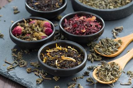assortment of dry tea in ceramic bowls, close-up