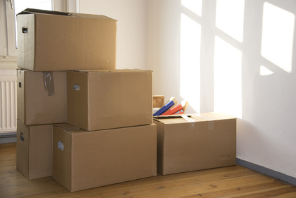 stacked moving boxes in a room with sun light