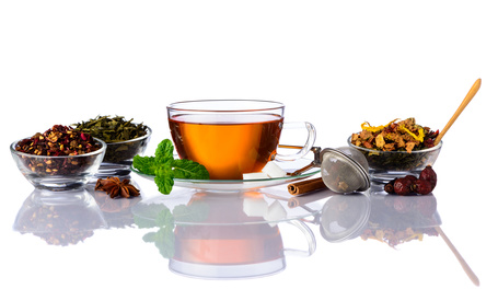 Cup of tea and different Tea ingredients isolated on white background